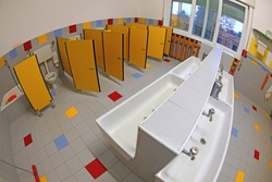 interior of the public bathroom of a kindergarten without children with small sinks and yellow doors photographed with fisheye lens