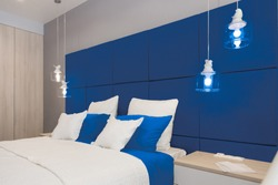 Interior of the room in light colors. Bedroom with bed and lighting classic blue color.  color of the year 2020 classic blue pantone