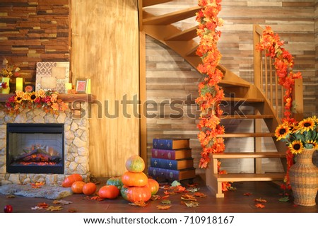 Interior of the room with a fireplace and a staircase in the autumn style with leaves, sunflowers and pumpkins