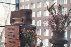 Interior of the room with old radio, wooden drawer, and vase with dry flowers.