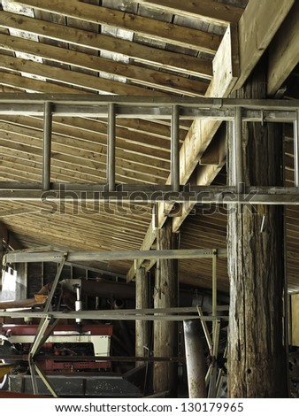 Interior of toolshed with old beams and aluminum, extension ladder by winter daylight on historical farm in northern Illinois