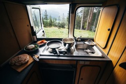 Interior of travel camping van or camper RV with stove and sink. Vanlife lifestyle vibes, cooking on campsite during road trip with amazing view of mountains. Life on the road in converted van