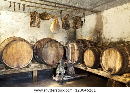 Interior of very old wine cellar with vintage wine pump and dried meat delicatessen-grunge brown toned