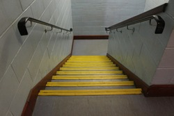 Interior office school staircase stairway, stone steps with yellow edging down perspective angle falling towards floor with bannister in wood and grey brick walls wooden railing & skirting boards