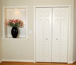 Interior photo of front closet and wall with decorated flower and light