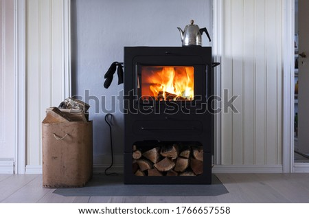 Interior photo with modern metal wood-burning stove; stove glove hanging at side, coffee kettle on stove and old box full of firewood standing on the left side.