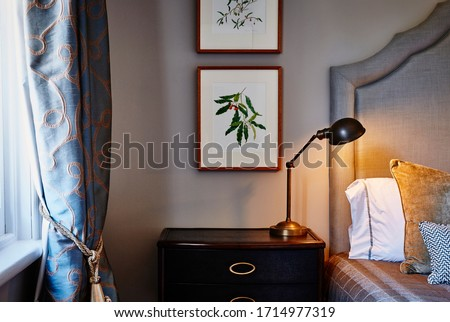 Interior photography of a loft bedroom in a Victorian mansion, a bed with an upholstered headboard, cushions, lamp, drapes and framed botanical illustrations