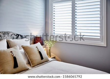 Interior photography of neutral toned bedroom with white bedding, upholstered bed head, tasseled cushions, bedside table and lamp, flowers and window with plantation shutters