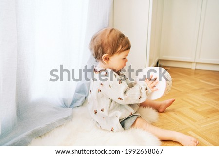 Interior portrait of adorable toddler girl sitting on the floor by the window, playing with toy drum