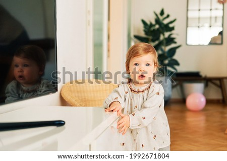 Interior portrait of funny toddler girl trying to open drawer