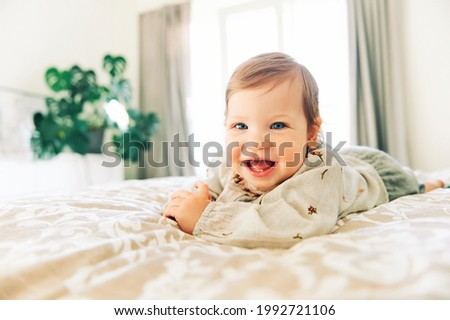 Interior portrait of happy laughing toddler girl lying on parent's bed
