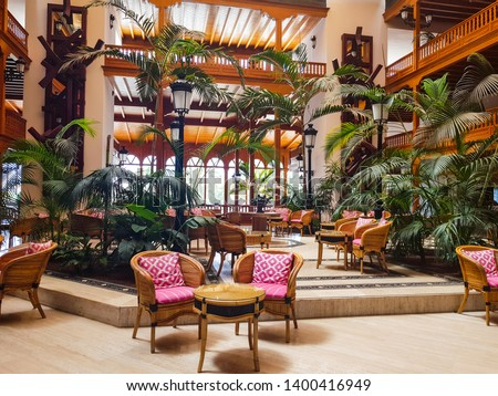 Interior reception of a hotel decorated with noble woods in colonial style and tropical vegetation