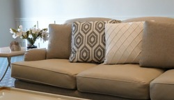 Interior scene of a couch with cushions in neutral tones of white and beige against a white background.