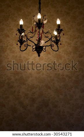 Interior scene of old chandelier over the wall with flowered pattern
