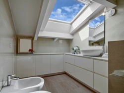 interior shot of a modern bathroom in the mansard with wood floor and the skylight