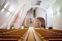 Interior shot of an large modern catholic church with high ceiling.