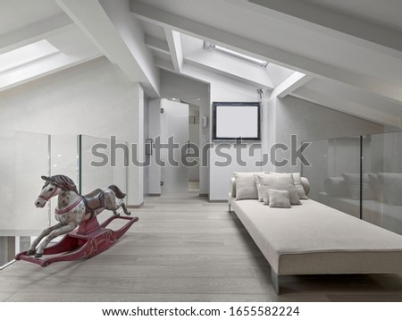 interior shots of a living room in the mansard in foreground the  fabric sofa and a old wooden rocking horse,  the floor is  made of wood