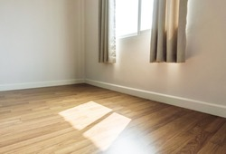 Interior space, empty room, laminate wooden floor with opened window receiving sunlight in the morning