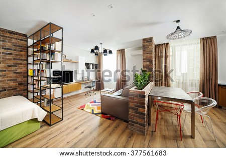 Interior studio apartments, with bookshelves and hardwood floors.