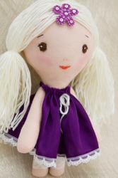 Interior toy doll with long hair. Handmade toy author. Rag doll for the decor in the nursery. Textile gift from natural materials. Decorative Toy in clothes. Pupa in a purple dress.