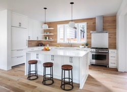 Interior view of a clean, bright kitchen with hardwood flooring, island and modern lighting.
