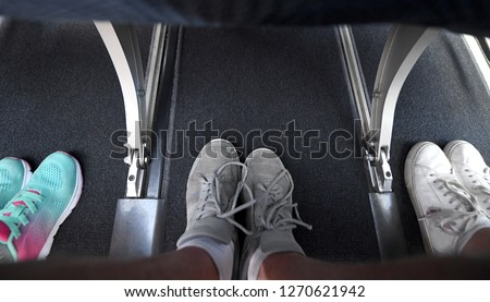 Interior view of a commercial airplane and its legroom in between seats.