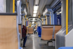 Interior view of a corridor inside passenger trains or light rail tram with blue fabric seats of German railway train system. Empty vacant passenger car inside the train.