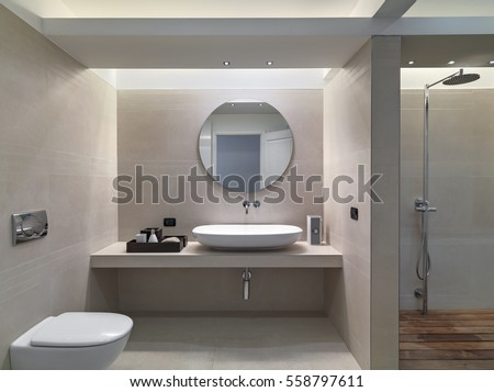 interior view of a modern bathroom in foreground the countertop washbasin whose walls are coated of pink marble overlooking on the shower cubicle