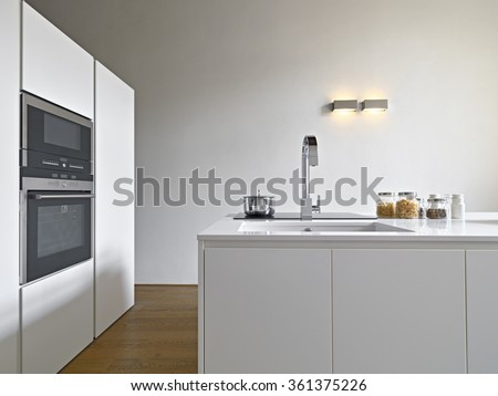interior view of a modern kitchen with kitchen island, sink and oven the floor is made of wood