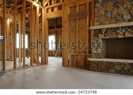 Interior view of a new home under construction. A stone fireplace has been installed. Horizontal shot.