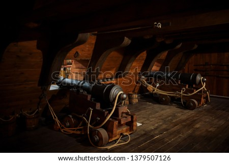 interior view of Cannons At The Deck and Cannon Balls plus windows on old galleon with ropes #1379507126