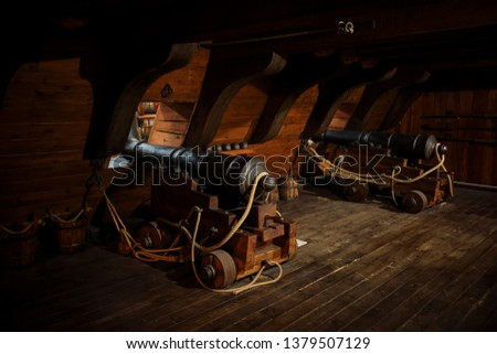 interior view of Cannons At The Deck and Cannon Balls plus windows on old galleon with ropes #1379507129