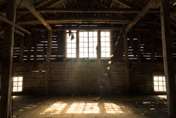 Interior view of the old village barn with old Windows and magical sunlight from it
