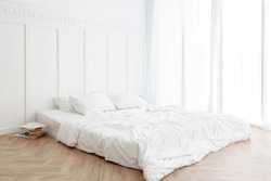 Interior view of white unmade messy bed on a wooden floor in the morning with transparent curtain and sunlight