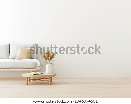 Interior wall mockup in warm neutrals with low sofa, beige pillow and dried Pampas grass on caned table in japandi style living room with empty white wall background. 3D rendering, illustration.