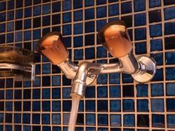 Interior water tap with two valve knobs and running water in bathroom with blue tiles on the wall