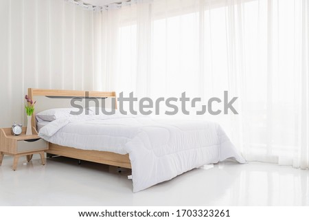 Interior white bedroom with white curtains and white pillows on wooden bed elegant classic for rest and sleep. Modern white bedroom bright.