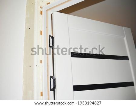 Interior white laminate door installation. Fitting the door, anchoring the door jamb and replacing hinge screws with split jambs undone.  Photo stock ©