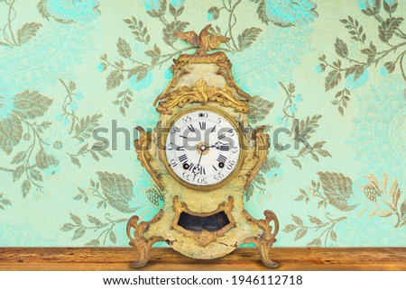 Interior with authentic eighteenth century weathered table clock in front of wallpaper with flower pattern Сток-фото ©