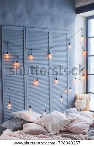 Interior with bed, blankets, garland and Edison lamps. Light colors, large window and blue wall