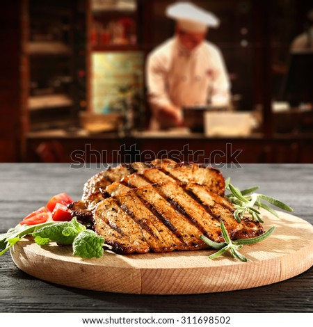 interior with cook of restaurant kitchen and steak on wooden desk top  #311698502