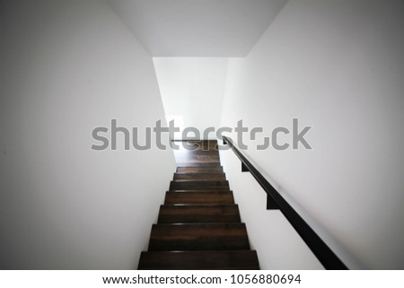 Interior wood stair with black steel handrail and railings and white walls #1056880694
