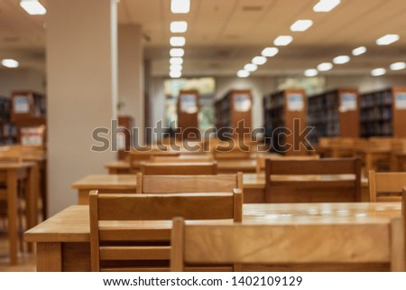 Interiors design wooden chairs and tables in the library room of university with the shelf books but nobody in the morning #1402109129