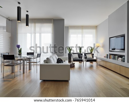 interiros shots of a modern living room in the foreground the leather sofa and the glass dining table the floor is made of wood