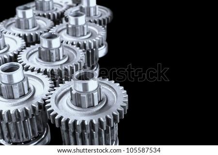 Interlocking industrial metal gears on black background