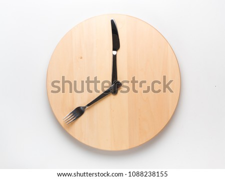 Intermittent fasting and skip breakfast concept - empty wooden round tray or trencher with cutlery as clock hands on white background. Eight hour feeding window concept or breakfast time concept