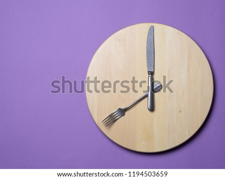 Intermittent fasting and skip breakfast concept - wooden round tray or trencher with cutlery as clock hands on lilac background. Eight hour feeding window concept or breakfast time concept. Copy space #1194503659