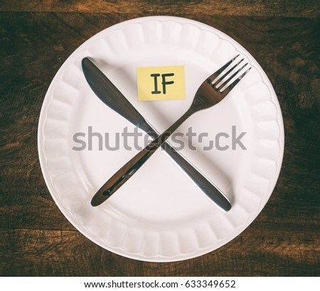 Intermittent fasting concept with knife and fork showing cross symbol on white plate with sticky note that reads IF, top view, vintage effect #633349652