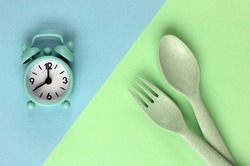 Intermittent fasting, diet and weight loss concept: clock, spoon and fork.  Intermittent, keto, detox, and slim diets. Flat lay, copy space.