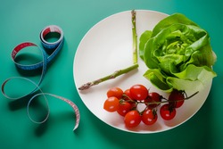 Intermittent fasting diet method - sixteen hours diet, eight hours eating time. White plate as clock with vegetables and centimeter tape on green background. Weight loss and healthy lifestyle.